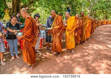 KRABI THAILAND - MAY 3 2015: Thai Buddhists offering food to monks' alms-bowl in Lanta island of Krabi Thailand