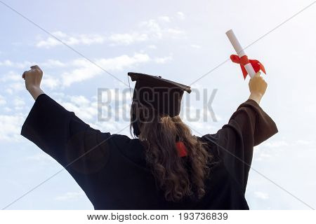 Graduate put her hands up and celebrating with certificate in her hand and feeling so happiness in Commencement day. Toned.