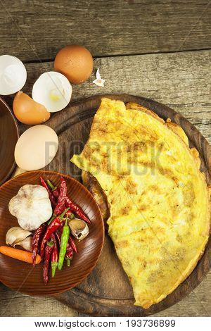 Delicious stuffed omelette on a wooden board. Fried egg omelette with cherry tomatoes garlic and chili peppers. Nutritious breakfast