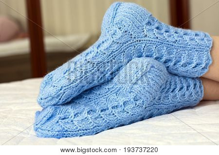 Female Legs Under The Blanket On The Bed In The Blue Woolen Socks. Cold Weather, Relaxation, Rest Ho