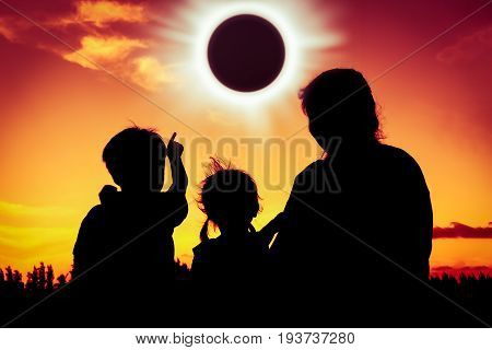 Silhouette back view of family sitting and relaxing together. Boy point to solar eclipse on gold sky background. Happy family spending time together. Outdoor.