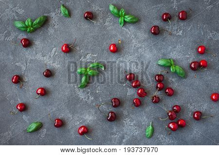 Cherry pattern. Fresh sweet cherry and basil leaves on black background. Flat lay top view