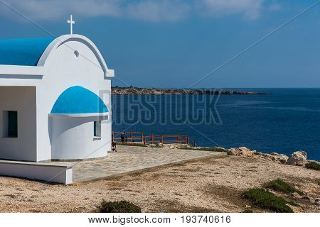 Traditional Greek White Chapel With A Blue Roof On The Seaside. Agioi Anargyroi Chapel, Cyprus