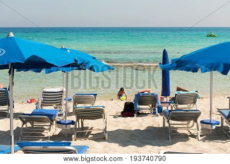 Tourists Relaxing On Sunbeds On A Sandy Beach Under Beach Umbrellas