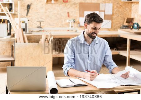 Joyful young woodworker with beard is sitting at table near laptop in workshop. He is holding graphite pencil in one hand and looking at paper sheet with smile. Copy space in left side