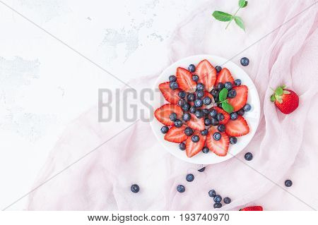 Fruit salad with strawberry and blueberry. Summer fresh fruits. Flat lay top view