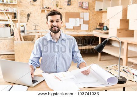 Waist up portrait of jolly young bearded wood master working on laptop at his table. He is holding piece of paper in one hand and typing something on computer keyboard by other hand