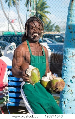 Nassau Bahamas - January 07 2016: happy muscular afroamerican man with smile break big fresh raw coconut smoking cigar outdoors