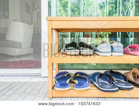 close up wooden shoes rack at the house door