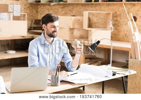 Joyful young bearded craftsman is sitting at table in workshop and holding wooden polygon in one hand. He is looking at it with smile while making some drafts on paper by graphite pencil