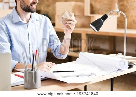 happy young bearded lumber craftsman sitting at workplace and holding timber polygon in his hand over paper sketches on desktop. Table lamp illuminating workplace