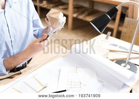 Close up of hands of young lumber craftsman making measurements of small timber polygon by means of beam-compass. Special table-lamp is illuminating desktop full of paper sketches
