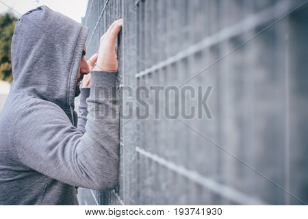 Lonely and sad Man Leaning against a Fence