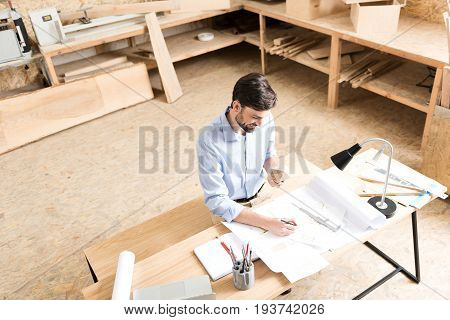 Top view of happy wood craftsman with beard sitting on bench at his desk and making drafts of new manufacture. He is drawing pictures on paper by graphite pencil. Copy space in left side