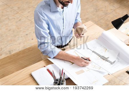 happy bearded lumber craftsman making draft of wooden produce on paper by pencil. He is holding timber polygon in other hand. Beam compass lying on sketches. Top view