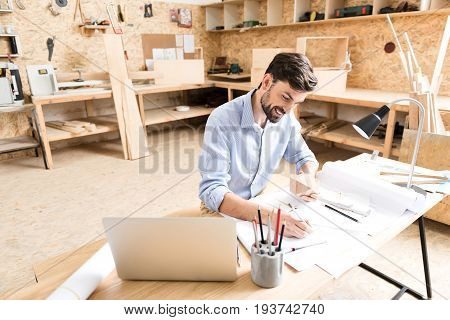 Happy young woodworker with beard is writing drafts of product design at table. He is smiling and holding lumber polygon in hand while making sketches in notebook by pencil. Copy space in left side