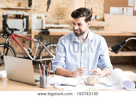 Waist up portrait of jolly bearded woodworker sitting at desk and looking at laptop screen with smile. He is leaning on paper sketches on table by his hands and holding pencil in them