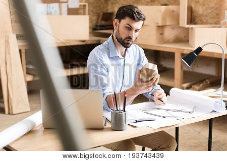 Pensive young timber craftsman with beard is sitting at table with lots of papers on it and looking intensely at wooden polygon, holding it in one hand. He is keeping graphite pencil in other hand