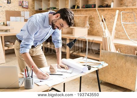 Happy young bearded woodworker is standing by his desk and drawing sketches in notebook by graphite pencil. He is leaning by other hand on draft pictures on table and smiling