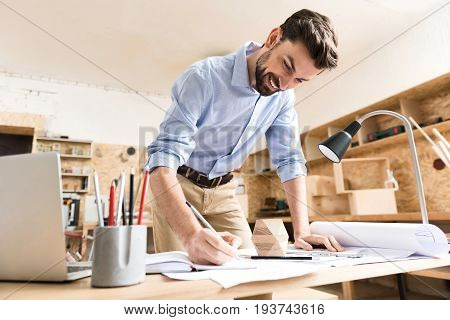 Jolly young woodworker with beard is standing nearby his table with smile and drawing sketches in notebook by graphite pencil. He is leaning on desktop by other hand. Low angle