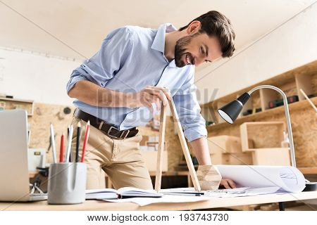 Happy youthful lumber craftsman with beard is standing near working table and making measurements by huge wooden divider. He is leaning on desk full of sketches by other hand. Low angle