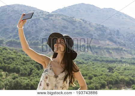 Woman traveler makes a self in the background beautiful natural view mountain on the island of Crete. Concept - tourism, travel, photos from vacation.
