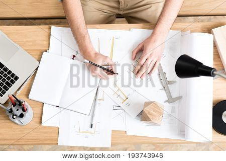 Close up of hands of lumber craftsman sitting at desk and drawing sketches by graphite pencil. Table lamp illuminating workplace. Top view
