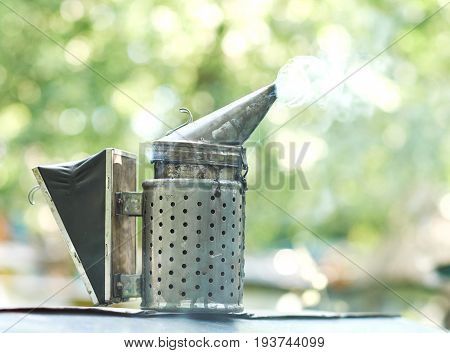 Bee smoker with smoke  copyspace beekeeping apiculture professional equipment technology tool concept.