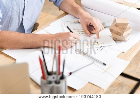 Close up of hands of woodworker sitting at desk and drawing sketches of lumber products. He is using graphite pencils and whatman paper in his job