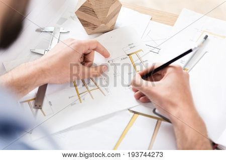 Close up of hands of lumber craftsman sitting at his working place and making calculations of future products dimensions. He is using graphite pencil and beam compass in his job. Top view