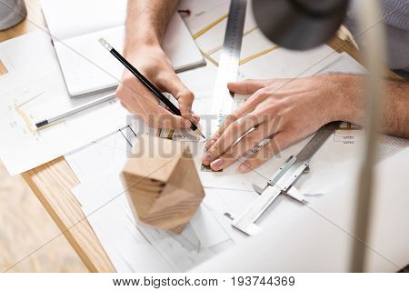 Close up of hands of woodworker sitting at desk and making calculations on sketches. He is using graphite pencil and long ruler. Beam compass and timber polygon lying on table. Top view