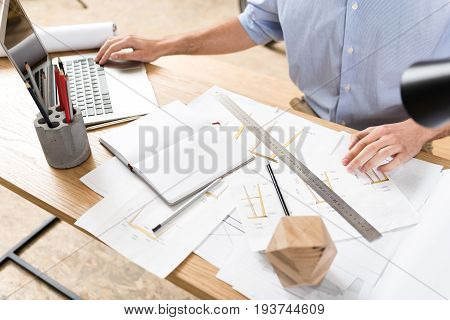 Close up of hands of wood designer sitting at desk full of sketches and typing something on laptop by one hand. Open notebook, graphite pencils, timber polygon and long ruler lying on table
