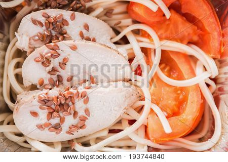 Healthy lunch in foil container. Fitness menu take away and delivery. Durum wheat pasta, steamed turkey, fresh vegetables and flax seeds in box, closeup