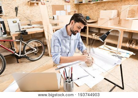 Happy young lumber craftsman with beard is holding wooden polygon and putting marks on it by graphite pencil at his desk in workshop. He is doing his job very attentively and carefully
