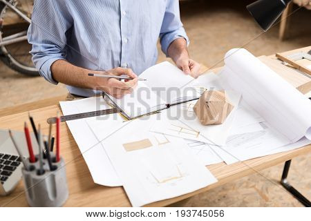 Close up of hands of woodworker sitting at his desk and making some notes in his notebook by graphite pencil. Different paper sketches, ruler and timber polygon lying on table