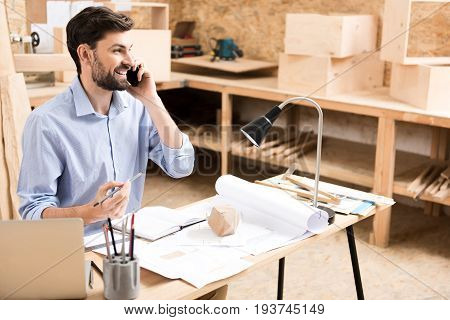 Happy young wood master with beard is sitting at desk and talking via mobile phone. He is holding graphite pencil in other hand over notebook lying on paper sketches on table. Copy space in right side