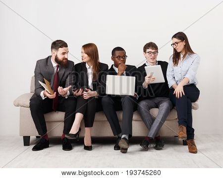Youn business team. Multiethnic people with devices discussing new marketing strategy, sitting on couch at modern office, full length, copy space