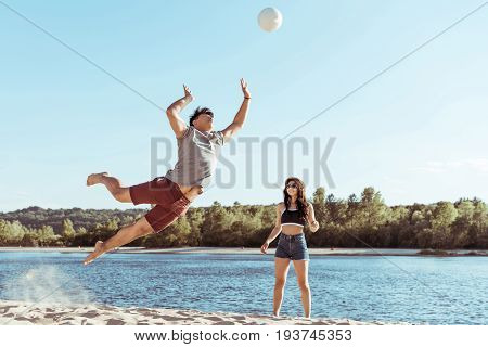 young friends playing volleyball on sandy beach at daytime poster