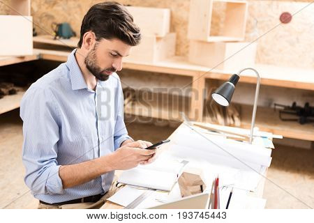 Worried young bearded lumber craftsman is sitting at table with lots of paper sketches and stationery. He is holding mobile phone in both hands and writing message