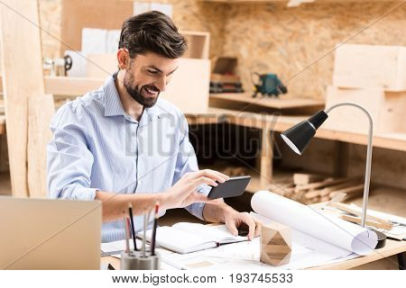 Cheerful young lumber master with beard is sitting at desk and making photo of wooden polygon lying on table over paper sketches. He is holding camera close to object by one hand and smiling