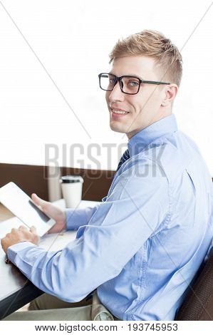 Closeup portrait of smiling adult business man turning to camera, using tablet computer and sitting at office desk. Side view.