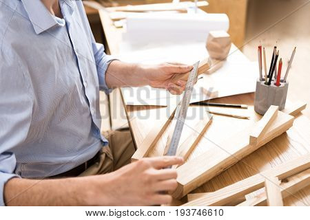 Close up of hands and body of lumber craftsman sitting at narrow desk and holding little plank in one hand and long aluminium ruler in other hand. He is measuring width of sticks lying on table