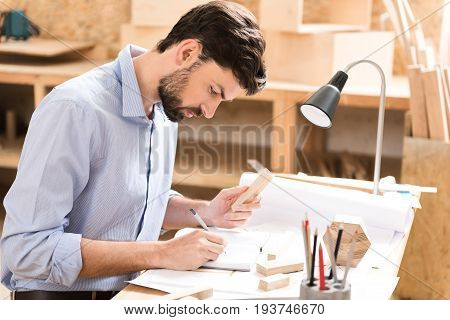 Serious young bearded lumber craftsman is sitting at workplace and making notes in notepad. He is holding little wooden stick in one hand and writing by graphite pencil