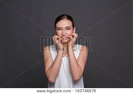 Young woman irritated, feeling squeamishness portrait. Attractive girl disgusted, grimacing at camera, dark background.
