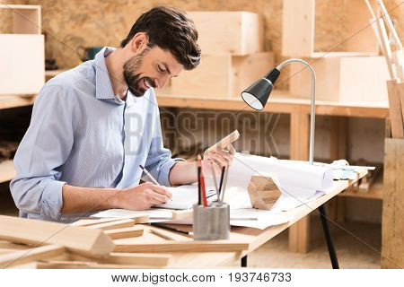Happy young bearded woodworker is sitting at his desk with many planks on it. He is putting down something in notepad by graphite pencil with smile and holding by other hand short timber stick