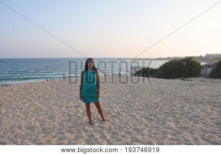 brunette girl in a short green sundress with a smooth southern sun on the sea background. evening on the beach