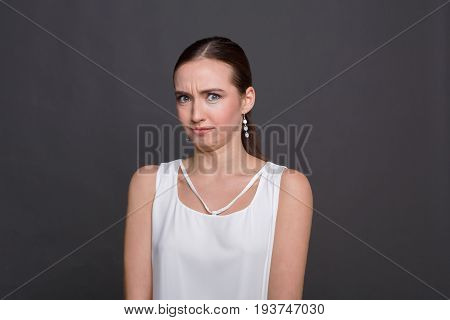 Bewildered attractive girl portrait. Shocked and surprised young woman looking at camera, dark background