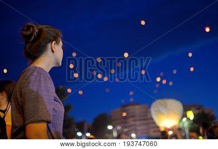 Teen Girl in summer night watching paper lantern