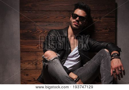 relaxed fashion man in sunglasses and leather jacket is sitting on wood background in studio