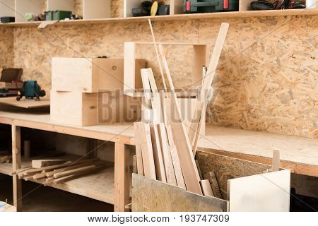Carpenter workshop with many shelves, which are holding variety planks of wood and some hand tools. Selective focus